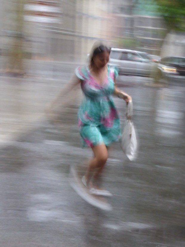 young woman in a Summer Dress running for shelter from the rain