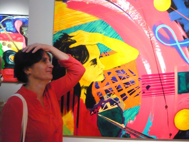 My wife next to a vividly coloured painting by Michael St Amand